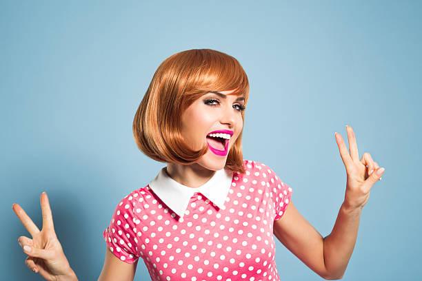 begeistert junge frau mit rot haare kleid mit pünktchenmuster - moderne 50er jahre mode stock-fotos und bilder
