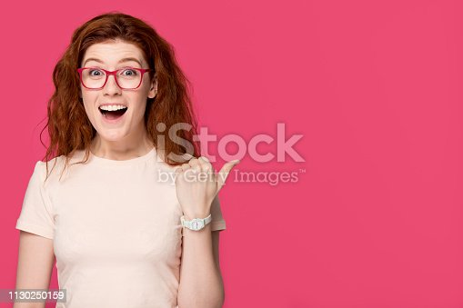 istock Excited redhead girl student in glasses advertising great sale offer 1130250159