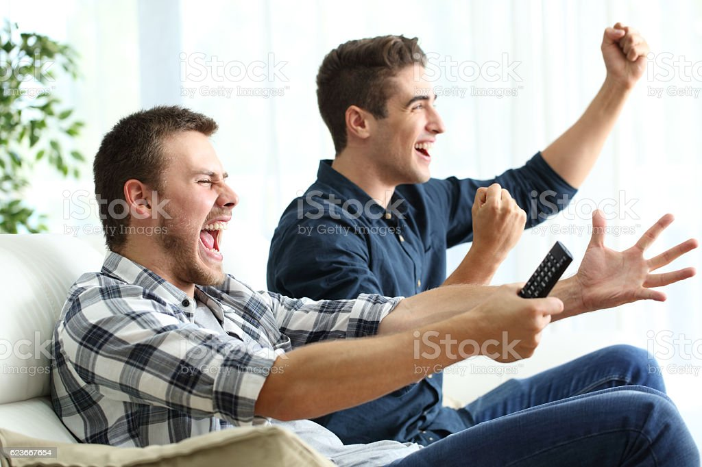 Excited roommates watching tv at home stock photo