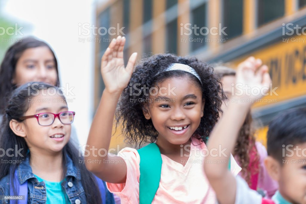 Excited school children board school bus stock photo