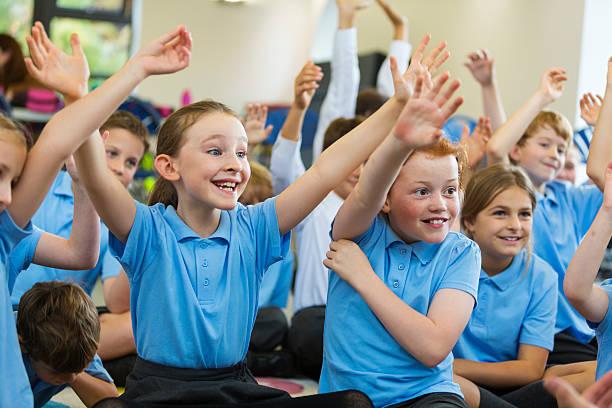 une los niños en edad escolar en uniforme con las manos arriba - escuela primaria fotografías e imágenes de stock