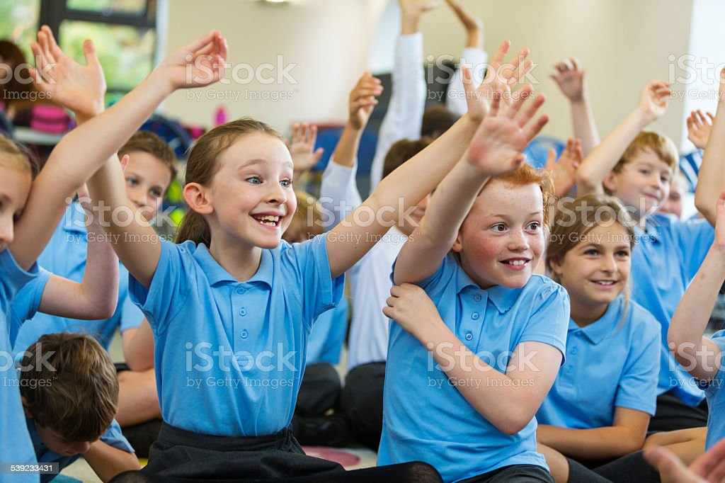 Excited School Children in Uniform with Hands Up stock photo