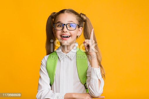 1176772377 istock photo Excited School Girl Pointing Finger Up Over Yellow Background 1173565509