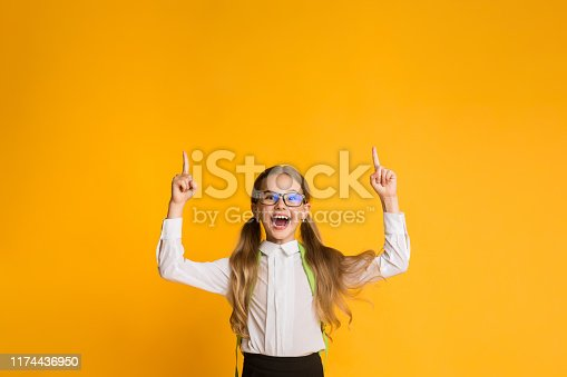 1176772377 istock photo Excited School Girl Pointing Fingers Up Over Yellow Background, Copyspace 1174436950