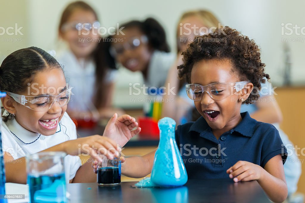 Excited school girls during chemistry experiment Diverse private school classmates are excited as foam overflows from beaker during chemistry experiment. Accuracy Stock Photo