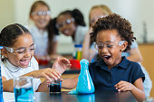 Excited school girls during chemistry experiment