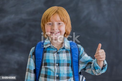 648947070istockphoto Excited schoolboy gives thumbs up on first day of school 648946966