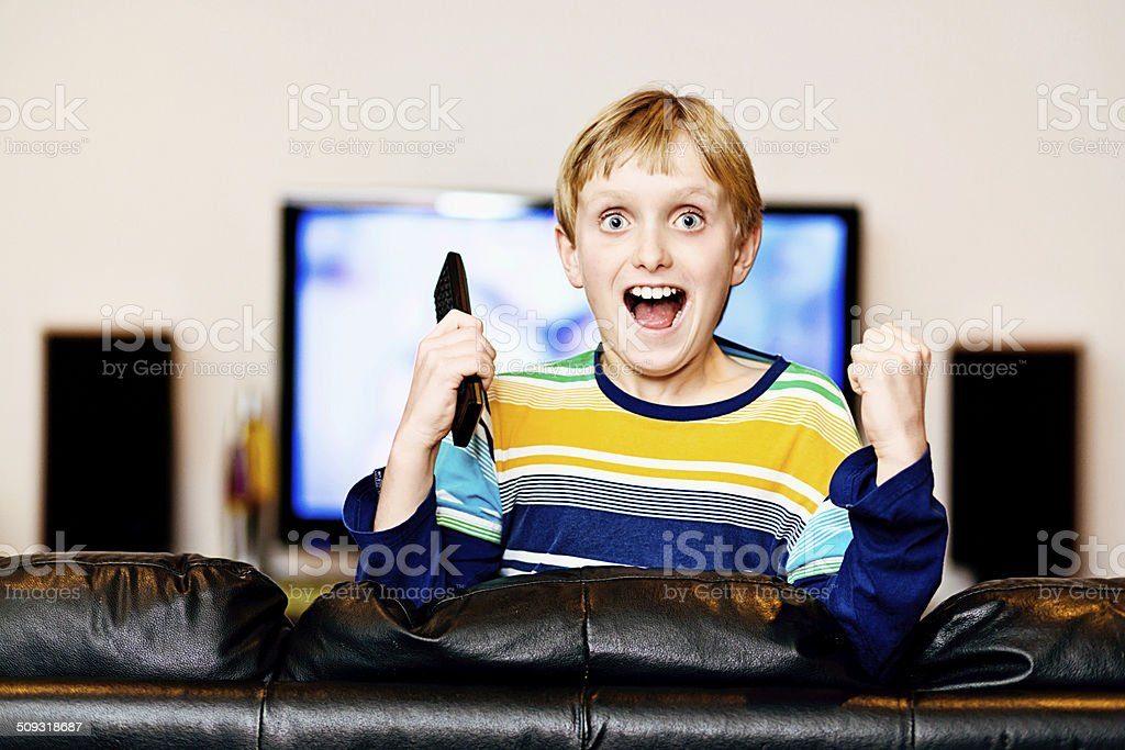 Excited schoolboy holding TV remote. What has he been watching?? stock photo