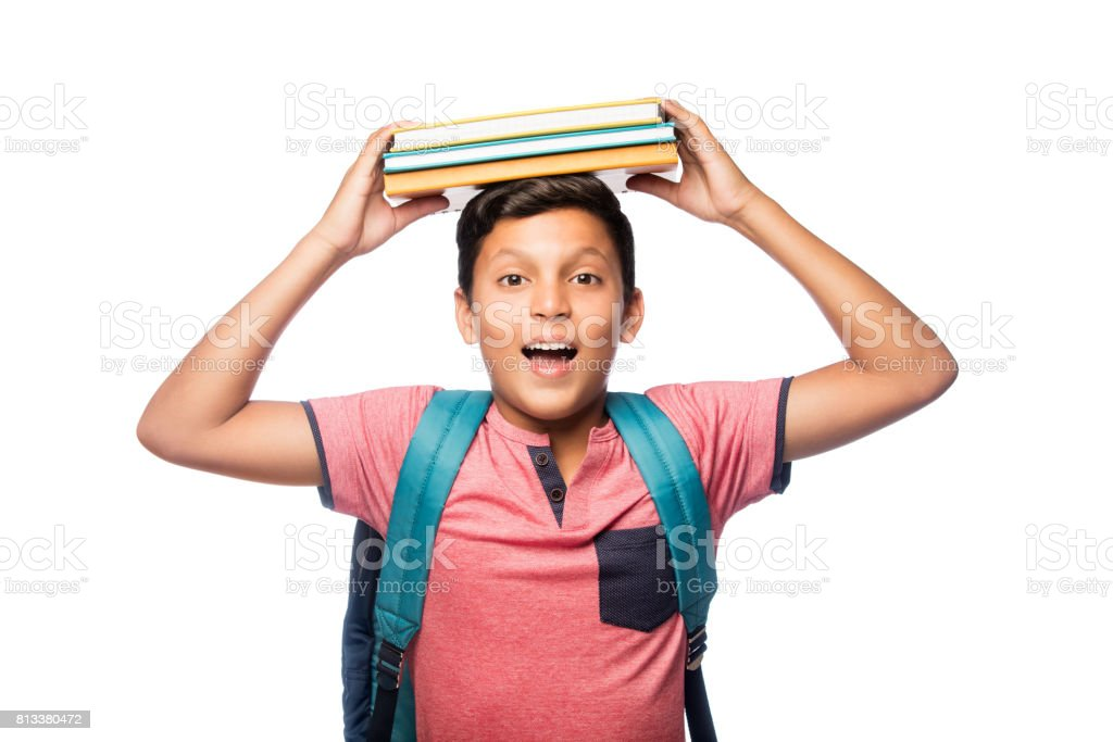 Excited schoolboy with books on top of head stock photo