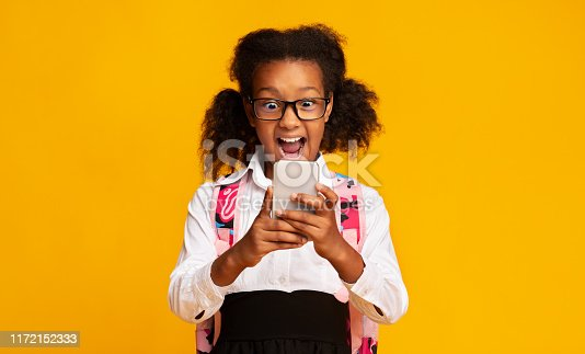 istock Excited Schoolgirl Using Smartphone On Yellow Background In Studio 1172152333