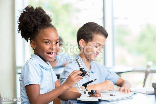 istock Excited schoolgirl works on school science project 610771646