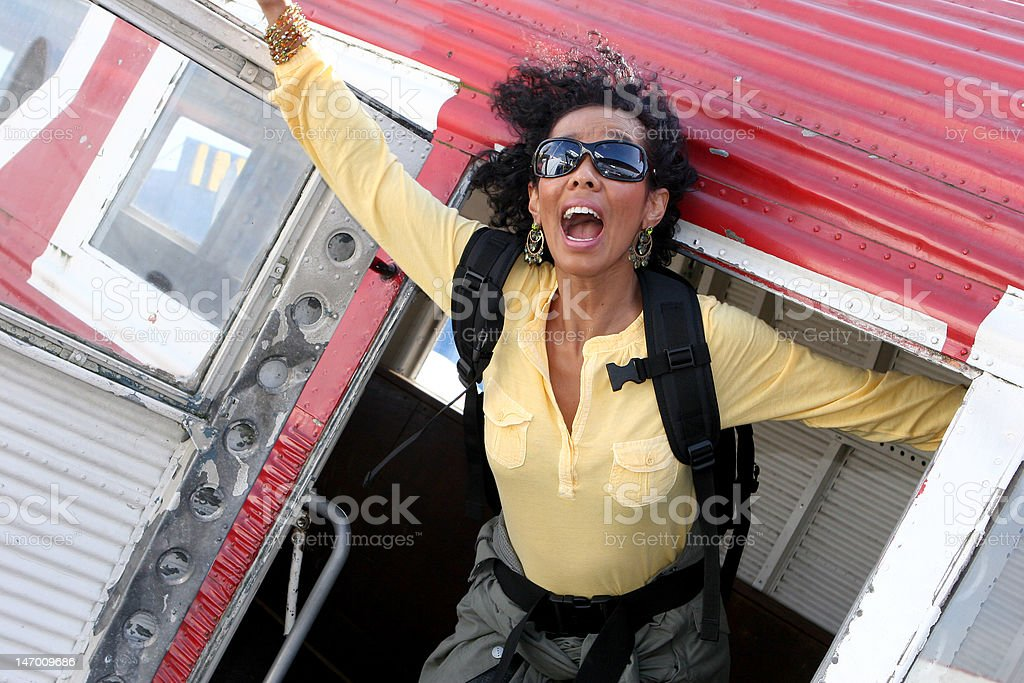 Excited, screaming young woman jumping out of a plane royalty-free stock photo