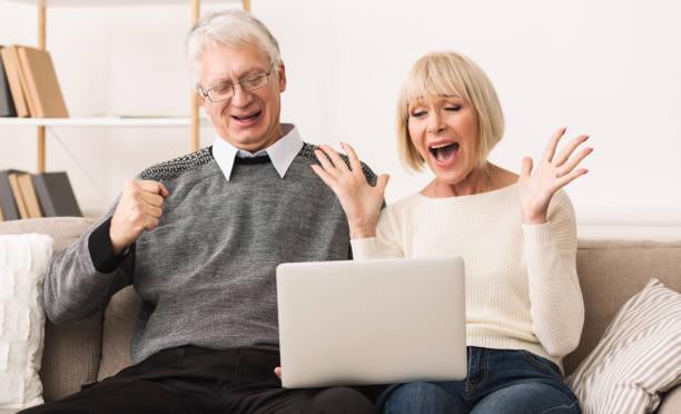 älteres paar feiert sieg, online-auktion zuschlag begeistert - versteigerung stock-fotos und bilder
