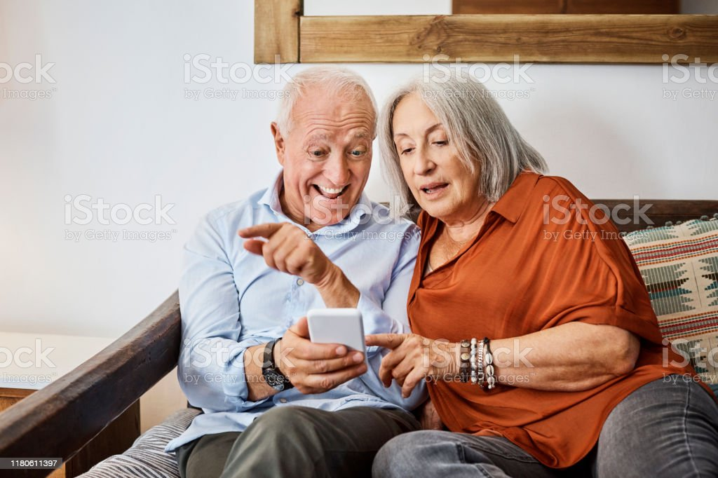 Excited senior couple looking at smart phone in house Excited senior man showing mobile phone to wife. Elderly couple are sitting on sofa. They are using technology at home. Active Seniors Stock Photo