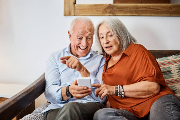 Excited senior couple looking at smart phone in house Excited senior man showing mobile phone to wife. Elderly couple are sitting on sofa. They are using technology at home. excited stock pictures, royalty-free photos & images