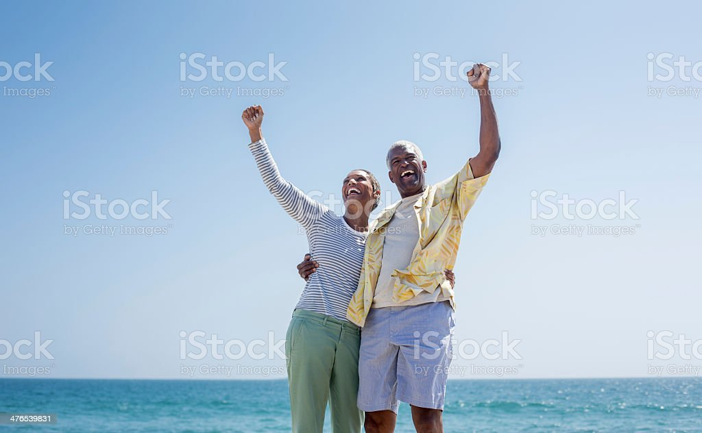 Excited senior couple raising arms stock photo