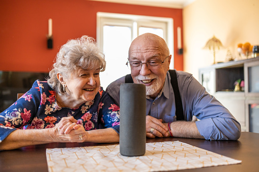Excited senior couple using a Virtual Assistant at home