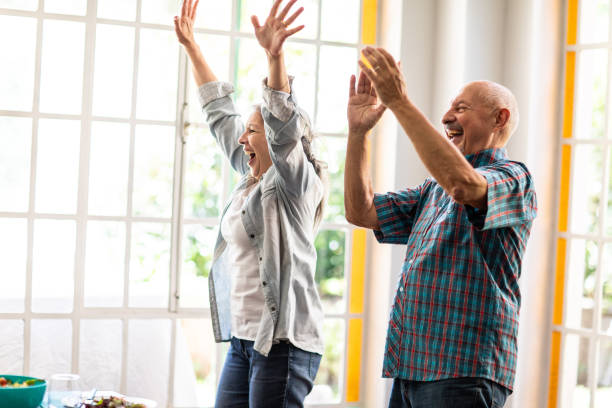 Excited senior couple with hands in the air Excited elderly married couple jumping with raised hands at home, looking happy excited stock pictures, royalty-free photos & images