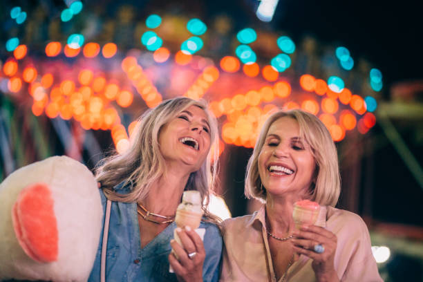 Excited senior friends eating ice cream on funfair night out stock photo