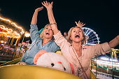 Happy mature women having fun on travelling carnival roller coaster ride with arms outstretched