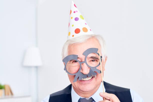 aufgeregt senior in der maske - schnurrbart themenpartys stock-fotos und bilder