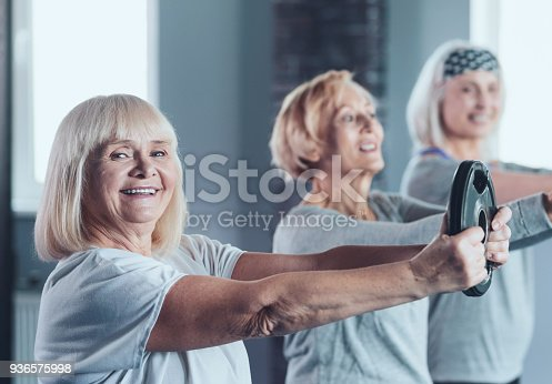 936573360istockphoto Excited senior lady holding weight disk while training 936575998