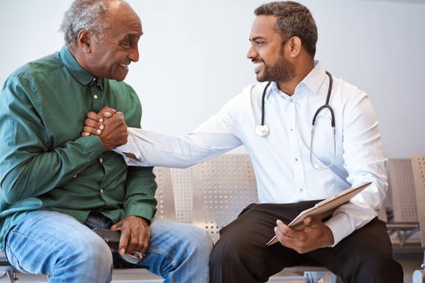 excited senior man shaking hands with doctor - buona notizia foto e immagini stock