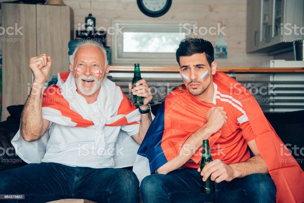 Homem sênior animado com garrafa de cerveja assistindo futebol com jovem - Foto de stock de Adulto royalty-free