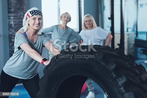 936573360 istock photo Excited senior woman leaning on heavy tire at gym 936576316