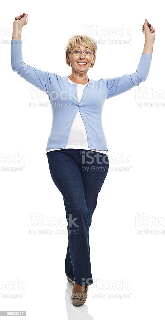 Excited senior woman Full lenght portrait of happy senior woman standing with raised hands. Studio shot, white background. 60-69 Years Stock Photo