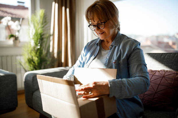 Excited senior woman unpacking online order stock photo
