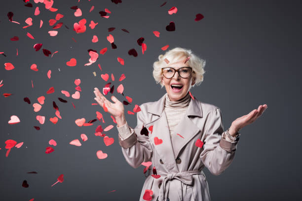 excited senior woman with confetti - senior valentine stock photos and pictures