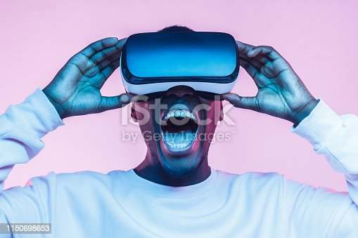 istock Excited shocked african man watching movie though VR glasses, screaming 1150698653