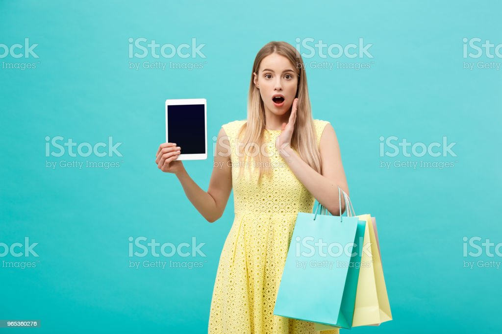 Excited shocked good-looking young woman in yellow dress while holding tablet and shopping bags. royalty-free stock photo