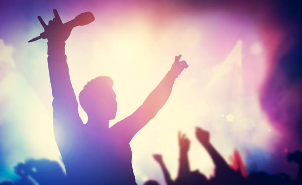 excited singer raising hands on stage. - rock musician stock pictures, royalty-free photos & images