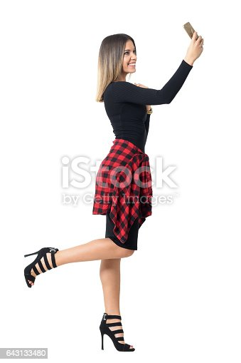 Excited smiling beauty taking selfie with one leg raised up. Side view. Full body length isolated over white studio background.
