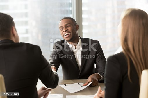 istock Excited smiling black businessman handshaking white partner at multiracial meeting 695760148