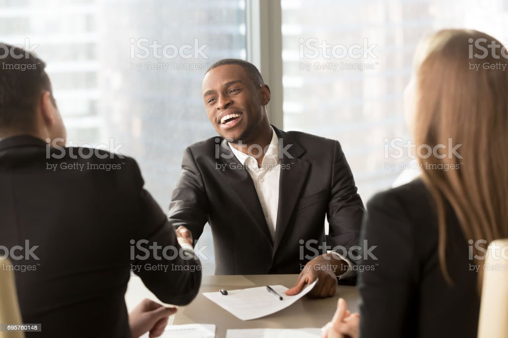 Excited smiling black businessman handshaking white partner at multiracial meeting stock photo