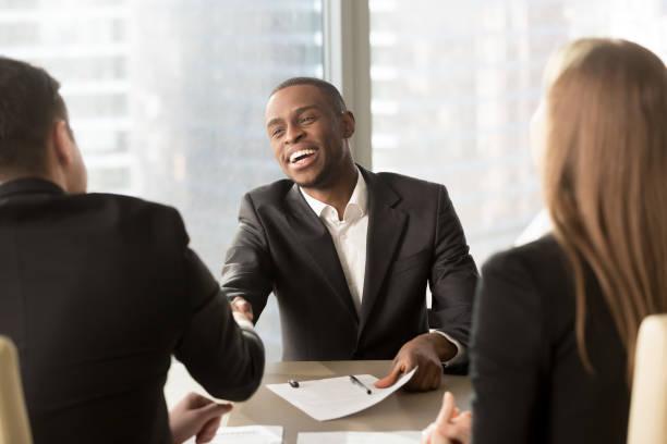 Aufgeregt, lächelnde schwarze Geschäftsmann Handshaking weißen Partner multirassische Tagung – Foto