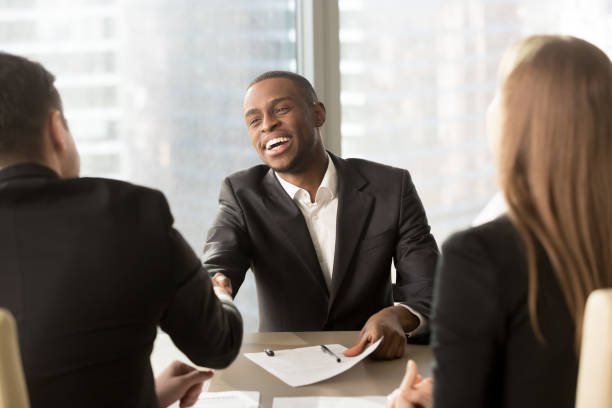 Excited smiling black businessman handshaking white partner at multiracial meeting stock photo