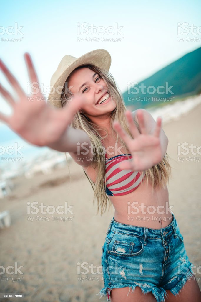 Excited Smiling Female with Outstretched Arms to You at Beach stock photo