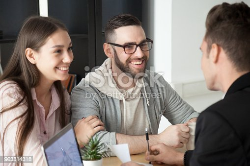 963814372 istock photo Excited smiling millennial couple discussing mortgage loan investment with realtor 963814318