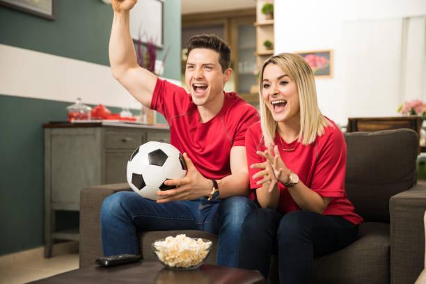 Fanáticos del fútbol emocionados viendo el juego - foto de stock