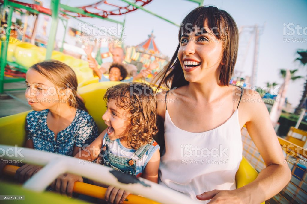 Excited son and daughter with mother on roller coaster ride stock photo
