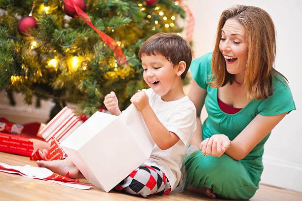 glücklich sohn eröffnung gegenwart mit mutter am heiligabend - geschenke eltern weihnachten stock-fotos und bilder