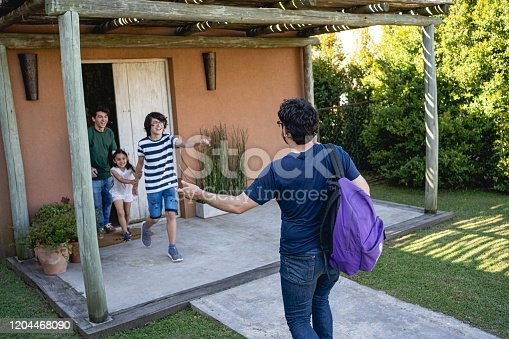 1196170672istockphoto Excited sons greeting father when he come back from trip 1204468090