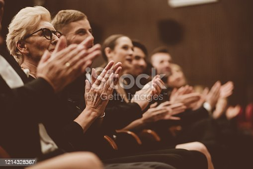 483876497 istock photo Excited spectators clapping in the theater, focus on hands 1214328367