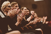 Side view of smiling audience clapping hands in opera house. Men and women are watching theatrical performance. They are in elegant wear.