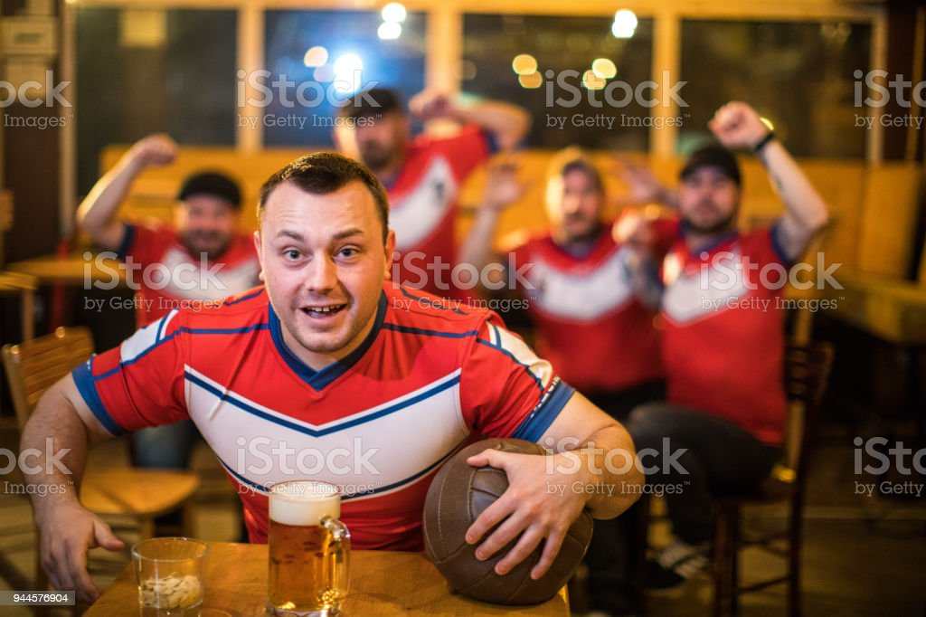 Group of sport fans watching a football game at the pub and drinking...