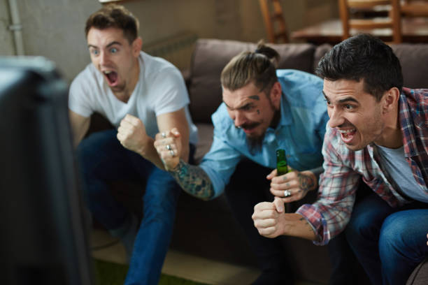 Excited Sport Fans Cheering for TV - foto de stock